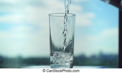 Pouring water in glass in slowmotion on blurred city and sky background.