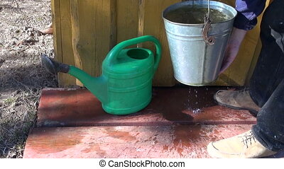 pouring water in watering can - Gardener pouring water from...