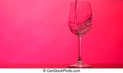 pouring water into a crystal glass on a red background