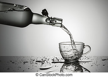 Pouring water into a glass cup.