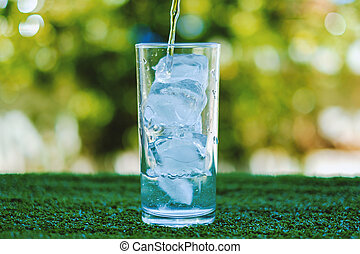 Pouring water into a glass of ice