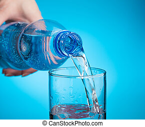Pouring water into a glass on a light blue background. Close-up, Side view.