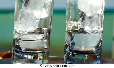 Pouring water into glasses with ice
