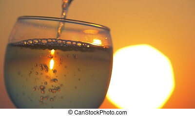Pouring water into the glass at sunset - Slow motion...