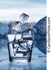 Pouring water with ice into a glass against the nature landscape