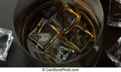 Pouring whiskey, cognac into glass with ice cubes. Pour of alcohol drink