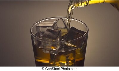 Pouring whiskey drink into glass with ice