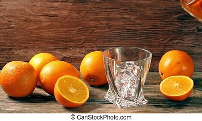 Pouring whiskey from bottle to glass over gray background with orange