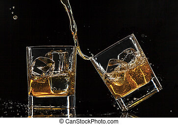 Pouring whiskey into glasses, isolated on black background