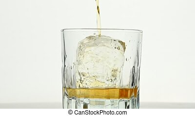 Pouring whiskey on ice rock in glass over white