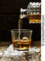 Pouring Whiskey or Scotch from carafe into a glass with ice cubes