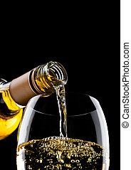 Pouring white wine from bottle to glass on black