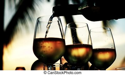 Pouring white wine in glass in slow motion at amazing sunset...