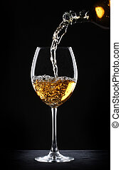 Pouring white wine into a glass over black background