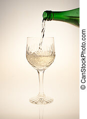 pouring white wine into crystal glass