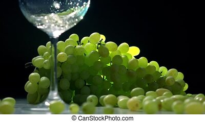 Pouring white wine into glass against the bunch of green grapes. Winemaking concept. Super slow motion shot