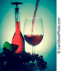 pouring wine in a glass next to a bottle of wine and grapes on a table with reflection on a vintage background