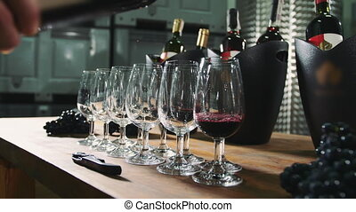 Pouring wine into wineglasses for degustation.
