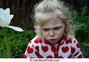 pouting girl - little blond girl in a garden pouting