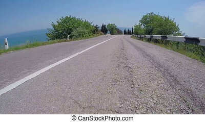 POV Car driving on curve coastal road down to the sea