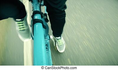POV cycling shot. Man's feet on bike pedals while riding...