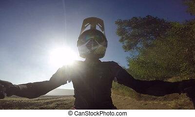 PoV: Enduro racer kicking up dust riding bike on dirt track against the sun