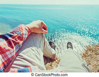 POV image of man sitting on coast