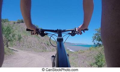 POV Mountain biking on trail along sea shore of Black Sea