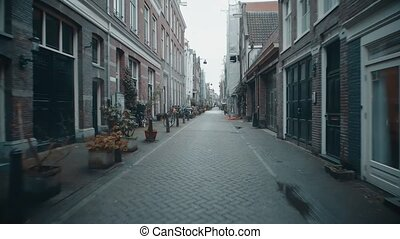 POV moving along typical narrow street in Amsterdam,...