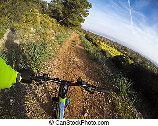 Mountain bike going downhill on a dirt path