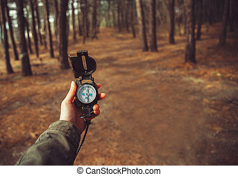 POV of hand with a compass - Hiker woman searching direction...