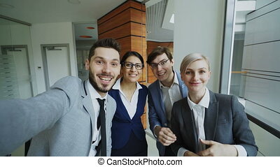 POV of Happy business team having online video chat using smartphone camera and talking to their colleague in modern office