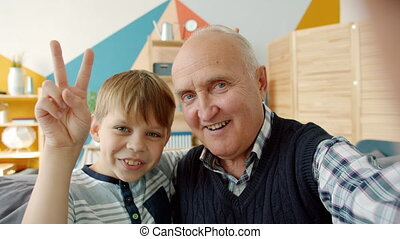 POV of happy grandfather and grandson taking selfie at home looking at camera smiling posing, child is showing v-sign hand gesture. People and photo concept.