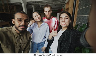 POV of happy multi-ethnic team have onlive video call and chatting with friends in modern office