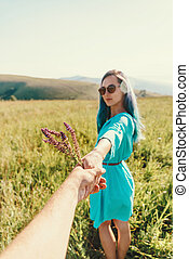 POV of loving couple together walking  in summer meadow.