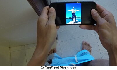 POV Of Man Sitting On Toilet Watching Photos On Cell Smart...