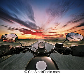 POV of motorbiker holding steering bar in beautiful sunset dramatic sky. Travel and freedom, outdoor activities. Motion blur