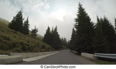 POV of mountain forest road seen from car driving through fog and mist in a gloomy day