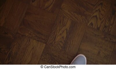 POV of person. Point of view of man walking indoors on wooden floor in blue sport casual shoes. 90 degree angle of person