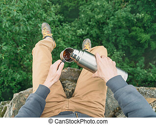 POV of traveler pouring tea from thermos