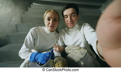 POV of Two young fencers man and woman have online video...
