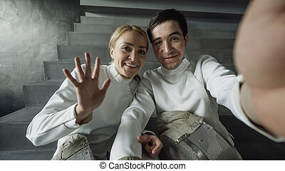 POV of Two young fencers man and woman have online video call with trainer using smartphone camera after fencing competition indoors