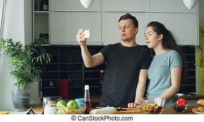 POV of Young happy couple having online video call with smartphone camera while cooking in the kitchen at home