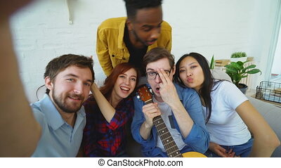 POV of young man with friends taking selfie photo on smartphone camera and have fun at home