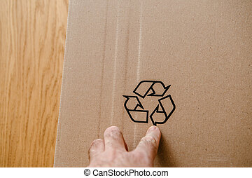 POV personal perspective of a male hand pointing to recycling sign on the cardboard box