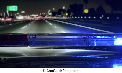 POV Police highway patrol car with red blue flash emergency lights driving on freeway at night.