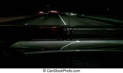 POV Police highway patrol car with red blue flash emergency lights driving