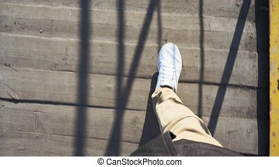 POV shot of a man's feet walking on the sidewalk with white ...