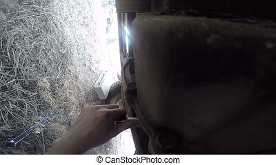 POV under car man repair propeller shaft.