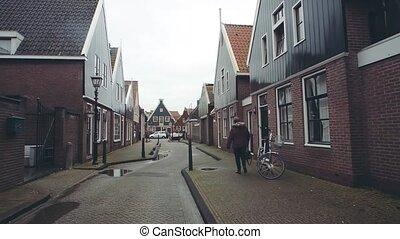 POV walk along traditional Dutch town street in Volendam,...